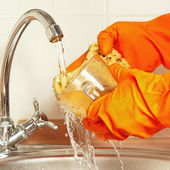 Hands in gloves wash the glass under running water in kitchen — Stock Photo