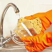 Hands in gloves with sponge wash dirty glass under running water — Stock Photo