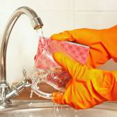 Hands in gloves wash the glass over the sink in kitchen — Stock Photo