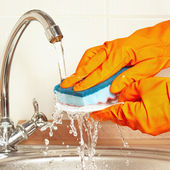 Hands in rubber gloves wash the dirty plate under running water in kitchen — Stock Photo