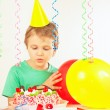 Little blonde boy in festive cap looking at birthday cake — Stock Photo #68680613