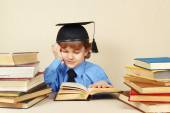 Little boy in academic hat studies old books — Stock Photo