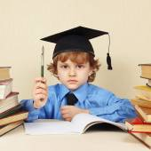 Little serious boy in academic hat with rarity pen among old books — Stock Photo