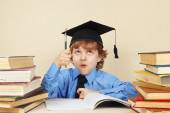 Little funny professor in academic hat with rarity pen among old books — Stock Photo