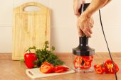 Hands cook are going to shred red pepper in blender — Stock Photo