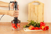 Hands chefs are going to shred red pepper in blender — Stock Photo