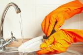 Hands in gloves wash dirty plate under running water in the kitchen — Stock Photo