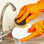 Hands in rubber gloves with sponge wash dishes under running water — Stock Photo