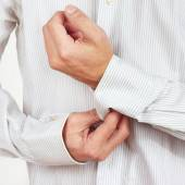 Hands a guy fastened the buttons on sleeve bright shirt closeup — Stock Photo