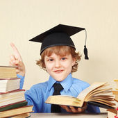 Little smiling boy in academic hat quoted old book — Stock Photo