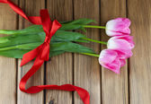 Top view of pink tulips with red ribbon and bow — 图库照片