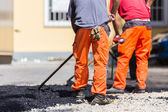 Asphalt surfacing manual labor. — Stock Photo