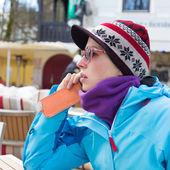 Vrouw in skigebied gebruikend smartphone. — Stockfoto