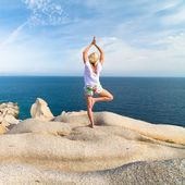 Woman practicing yoga at the beach. — Stock Photo
