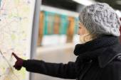 Lady looking on public transport map panel. — Stock Photo