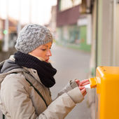 Young lady posting letters. — Stock Photo