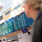 Female traveller checking flight departures board. — Stock Photo