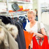 Beautiful woman shopping in clothing store. — Stock Photo