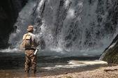 Senior fisherman catching fishes in fresh stream — Stock Photo