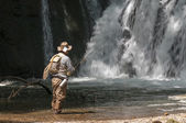 Senior fisherman catching fishes in fresh stream — Stock Photo
