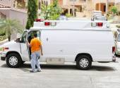 White ambulance with the driver getting out to help the paramedi — Stock Photo