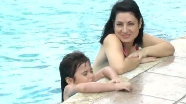 Happy mother and daughter girl at swimming pool in summer vacation — Stock Video