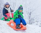 Family having fun with sled in winter park — Stock Photo