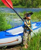 Boy near a kayak on the river — ストック写真