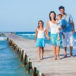 Family walking wooden jetty — Stock Photo #72826135