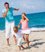 Kids and father playing on the beach. — Stock Photo