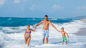 Father and children playing on the beach — Stock Photo