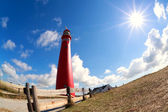 Red lighhouse tower and sun star — Stock Photo