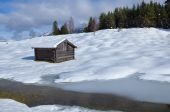Old wooden hut on snowy alpine meadow — Stock Photo