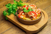 Roast veal with tomato and potato on clay pan — Stock Photo