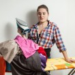 Housewife holding iron and looking at pile of clothes — Stock Photo #52302561
