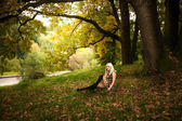 Blonde woman sitting under big tree at autumn park — Stock Photo