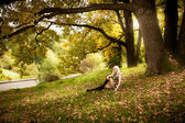 Sexy woman relaxing under old oak tree at autumn — Stock Photo