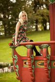 Cute woman sitting on handrail at pagoda — Stock Photo