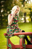 Blonde woman sitting in chinese gazebo at park — Stock Photo