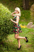Slim woman posing at garden against bush — Stock Photo
