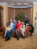 Happy family sitting on sofa at living room at christmas eve — Stock Photo