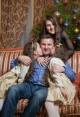 Daughters kissing and hugging dad at christmas eve — Stock Photo