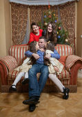 Father kissing daughters on sofa at christmas eve — Stock Photo