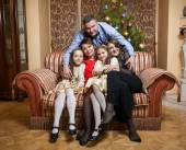 Father hugging big family seated on sofa at christmas day — Stock Photo