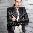 Sexy brunette man in leather coat leaning against wooden wall — Stock Photo #52685603