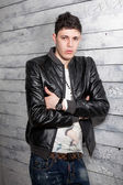 Sexy brunette man in leather coat leaning against wooden wall — Photo