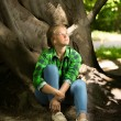 Woman in casual clothes sitting under big tree at forest — Stock Photo #54849183