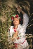 Portrait of girl in ukrainian clothes lying in high grass — Stock Photo