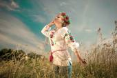 Beautiful woman in ukrainian clothes at field at windy day — Stock Photo