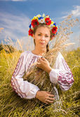 Ukrainian woman in embroidered shirt holding sheaf of wheat — Stock Photo